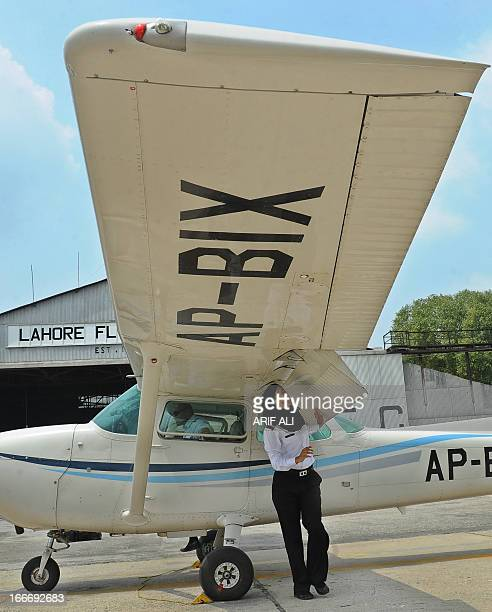 In this photograph taken on August 6 eighteen year old Pakistani female flying student Qadar Sarfraz inspects her small Cessna plane before taking...