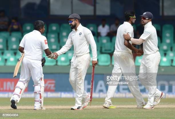 In this photograph taken on August 6 Indian cricket captain Virat Kohli is congratulated by Sri Lankan cricketer Rangana Herath after victory in the...