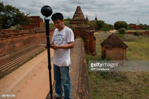 In this photograph taken on August 6 Nyi Lin Seck looks at his 3604K video camera while documenting the crumbling 700yearold walls of the ancient...