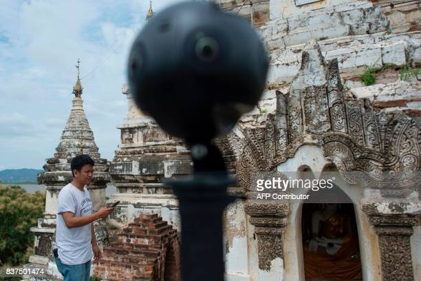 In this photograph taken on August 6 Nyi Lin Seck stands next to a 3604K video camera as he documents the crumbling 700yearold walls of the ancient...
