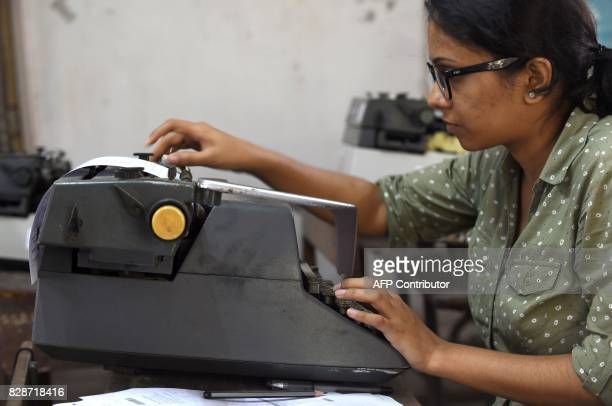 In this photograph taken on August 7 a candidate adjusts her answer sheet on a typewriter as she appears for the last official typing exam conducted...