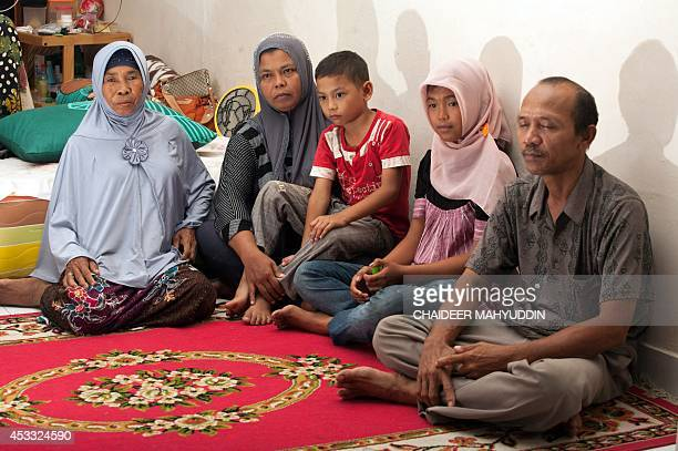 In this photograph taken on August 7 missing Indonesian tsunami victim Raudhatul Jannah aged 14 sits with mother Jamaliah holding youngest son Jumadi...