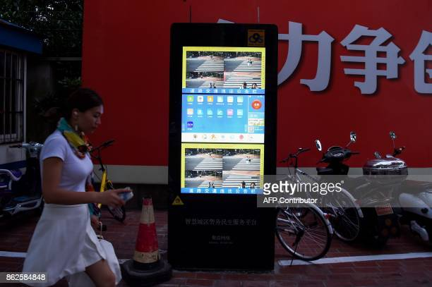 In this photograph taken on August 9 2017 a Chinese girl walks past the installed facial recognition screen at a road intersection in Shanghai From...