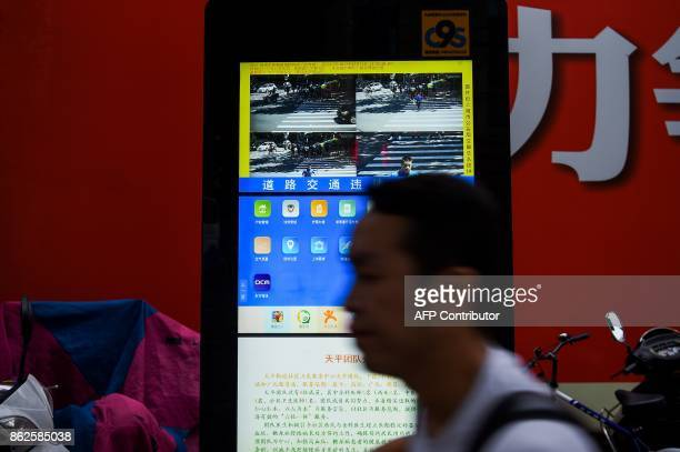 In this photograph taken on August 9 2017 a Chinese man walks past the installed facial recognition screen at a road intersection in Shanghai From...