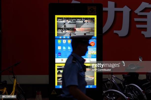 In this photograph taken on August 9 2017 a Chinese traffic policeman walks past the installed facial recognition screen at a road intersection in...