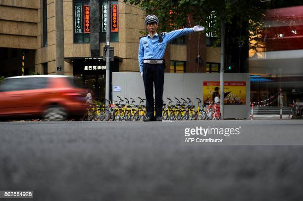 In this photograph taken on August 9 2017 a Chinese traffic policeman manages traffic at a road intersection in Shanghai From toiletpaper dispensers...