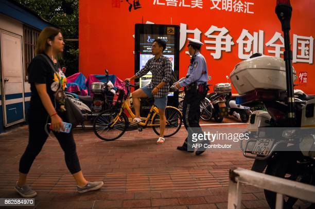 In this photograph taken on August 9 2017 a Chinese traffic policeman prepares to talk to a man about riding bicycle and offending traffic rules next...