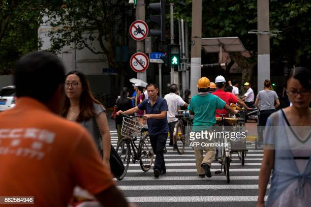 In this photograph taken on August 9 2017 Chinese people cross a road in Shanghai From toiletpaper dispensers to fastfood restaurants travel and...