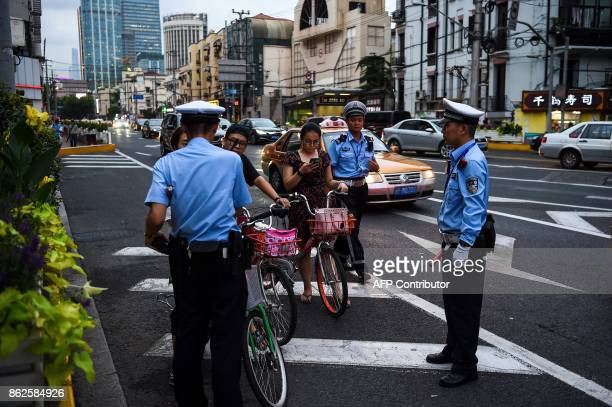 In this photograph taken on August 9 2017 Chinese traffic policemen stop a group of people riding bicycles and offending traffic rules next to the...