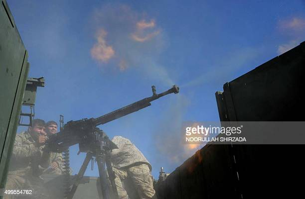 In this photograph taken on December 1 a member of the Afghan security force fires during an ongoing operation against Islamic state groups in Achin...