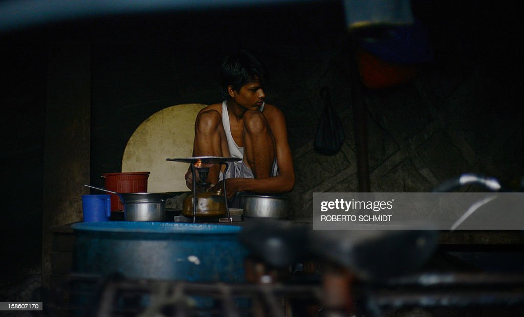 In this photograph taken on December 11, 2012 a boy cooks a chapati over a gas stove at an open air laundry facility known as the Dhobi Ghat in Mumbai. This 25-acre (10-hectare) space is a chaotic conglomeration of rows of open-air concrete wash pens, each with its own flogging stone and rooms where the washermen, also known as 'dhobiwallahs', sleep and work. Many of the over 700 families that make a living out of this Dhobi Ghat, who had followed their father into the business, a life of dunking, thrashing and drying close to 1,000 items of clothing each day for just 7 USD, are worried about the future as the workload has gone down considerably. Most ordinary Indians who have seen their disposable incomes rise as the country's economy expands, have dispensed with the services of the dhobiwallahs for good since most modern homes are equipped with a washing machine. AFP PHOTO / Roberto Schmidt