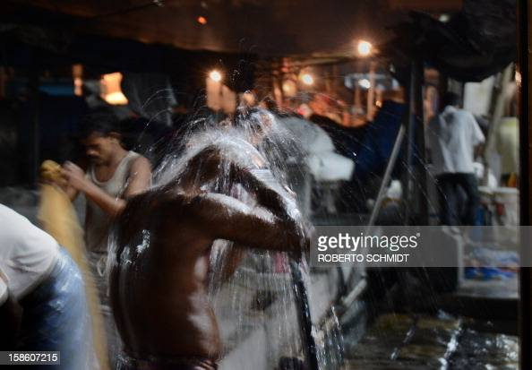 In this photograph taken on December 11 2012 a man bathes at the end of the day as others continue to wash clothes at an open air laundry facility...