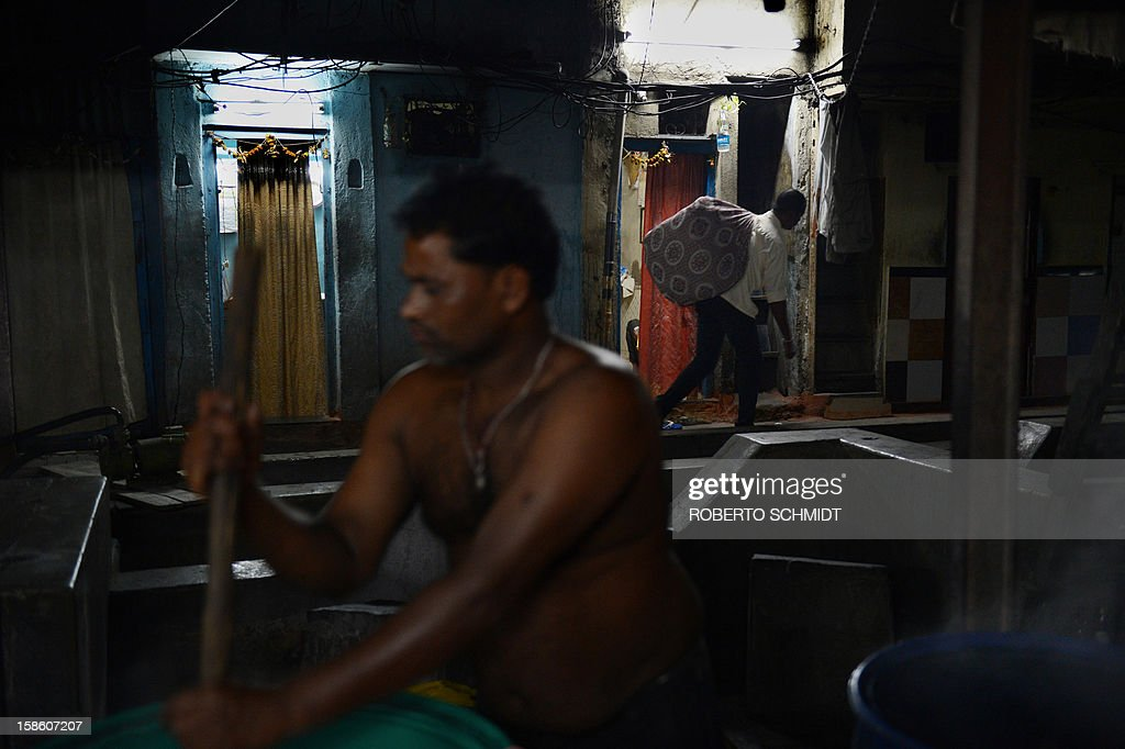 In this photograph taken on December 11, 2012 a man carries a bunch of cleaned clothes on his back as another one stirs clothes in hot water (L) at an open air laundry facility known as the Dhobi Ghat in Mumbai. This 25-acre (10-hectare) space is a chaotic conglomeration of rows of open-air concrete wash pens, each with its own flogging stone and rooms where the washermen, also known as 'dhobiwallahs', sleep and work. Many of the over 700 families that make a living out of this Dhobi Ghat, who had followed their father into the business, a life of dunking, thrashing and drying close to 1,000 items of clothing each day for just 7 USD, are worried about the future as the workload has gone down considerably. Most ordinary Indians who have seen their disposable incomes rise as the country's economy expands, have dispensed with the services of the dhobiwallahs for good since most modern homes are equipped with a washing machine. AFP PHOTO / Roberto Schmidt