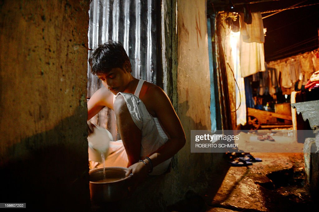 In this photograph taken on December 11, 2012 a man cooks in the room where he live and that he rents for a fee at an open air laundry facility known as the Dhobi Ghat in Mumbai. This 25-acre (10-hectare) space is a chaotic conglomeration of rows of open-air concrete wash pens, each with its own flogging stone and rooms where the washermen, also known as 'dhobiwallahs', sleep and work. Many of the over 700 families that make a living out of this Dhobi Ghat, who had followed their father into the business, a life of dunking, thrashing and drying close to 1,000 items of clothing each day for just 7 USD, are worried about the future as the workload has gone down considerably. Most ordinary Indians who have seen their disposable incomes rise as the country's economy expands, have dispensed with the services of the dhobiwallahs for good since most modern homes are equipped with a washing machine. AFP PHOTO / Roberto Schmidt