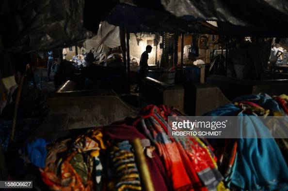 In this photograph taken on December 11 2012 a washer stands near clothes waiting to be washed at an open air laundry facility known as the Dhobi...