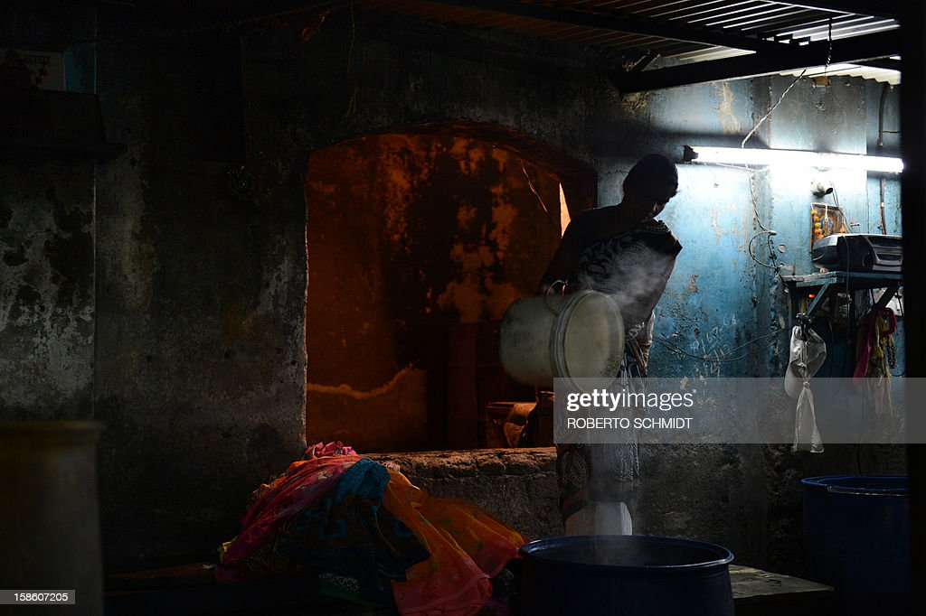 In this photograph taken on December 11, 2012 a woman pours boiling water into a drum where along with soap, clothes will be left soaking overnight before being washed the next day at an open air laundry facility known as the Dhobi Ghat in Mumbai. This 25-acre (10-hectare) space is a chaotic conglomeration of rows of open-air concrete wash pens, each with its own flogging stone and rooms where the washermen, also known as 'dhobiwallahs', sleep and work. Many of the over 700 families that make a living out of this Dhobi Ghat, who had followed their father into the business, a life of dunking, thrashing and drying close to 1,000 items of clothing each day for just 7 USD, are worried about the future as the workload has gone down considerably. Most ordinary Indians who have seen their disposable incomes rise as the country's economy expands, have dispensed with the services of the dhobiwallahs for good since most modern homes are equipped with a washing machine. AFP PHOTO / Roberto Schmidt