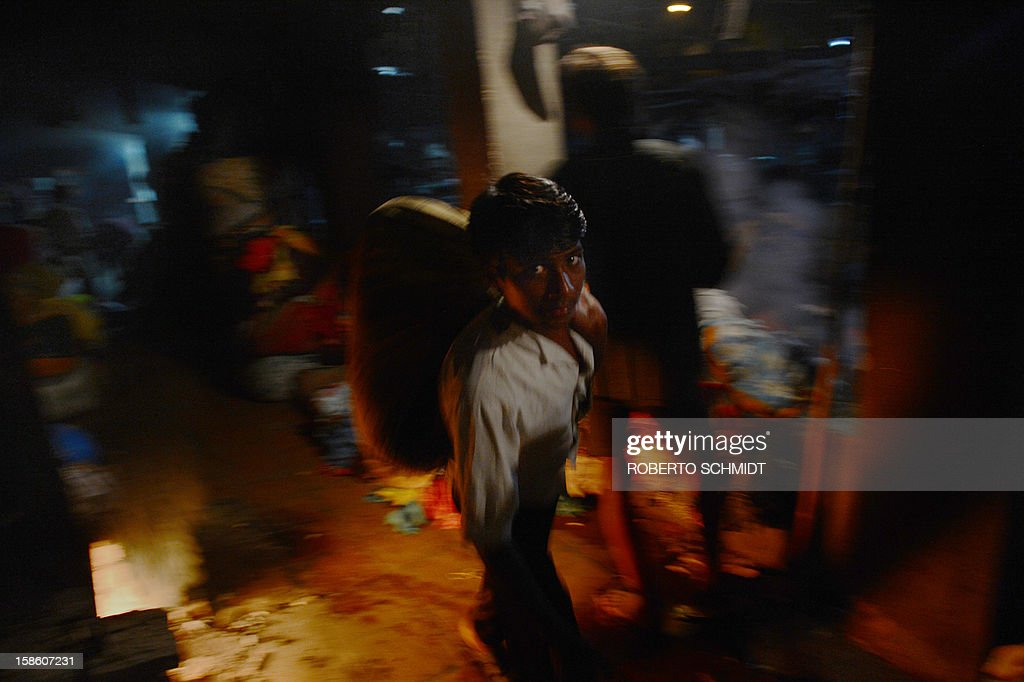In this photograph taken on December 11, 2012 a worker carries a bunch of clothes on his back past a drum filled with water to be boiled (L) at an open air laundry facility known as the Dhobi Ghat in Mumbai. This 25-acre (10-hectare) space is a chaotic conglomeration of rows of open-air concrete wash pens, each with its own flogging stone and rooms where the washermen, also known as 'dhobiwallahs', sleep and work. Many of the over 700 families that make a living out of this Dhobi Ghat, who had followed their father into the business, a life of dunking, thrashing and drying close to 1,000 items of clothing each day for just 7 USD, are worried about the future as the workload has gone down considerably. Most ordinary Indians who have seen their disposable incomes rise as the country's economy expands, have dispensed with the services of the dhobiwallahs for good since most modern homes are equipped with a washing machine. AFP PHOTO / Roberto Schmidt