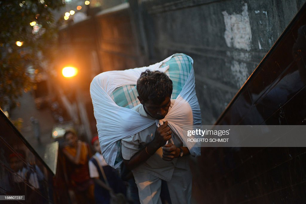 In this photograph taken on December 11, 2012 a worker carries a load of clean clothes to be delivered after being washed and ironed as he leaves an open air laundry facility known as the Dhobi Ghat in Mumbai. This 25-acre (10-hectare) space is a chaotic conglomeration of rows of open-air concrete wash pens, each with its own flogging stone and rooms where the washermen, also known as 'dhobiwallahs', sleep and work. Many of the over 700 families that make a living out of this Dhobi Ghat, who had followed their father into the business, a life of dunking, thrashing and drying close to 1,000 items of clothing each day for just 7 USD, are worried about the future as the workload has gone down considerably. Most ordinary Indians who have seen their disposable incomes rise as the country's economy expands, have dispensed with the services of the dhobiwallahs for good since most modern homes are equipped with a washing machine. AFP PHOTO / Roberto Schmidt