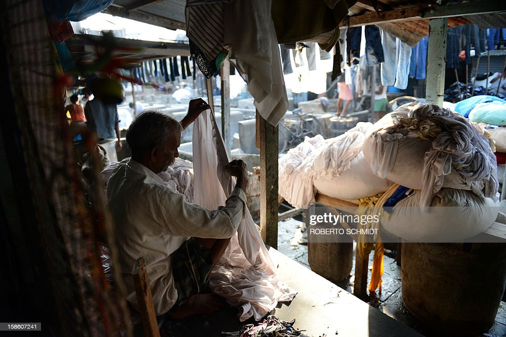 In this photograph taken on December 11, 2012 a worker checks for thumbnail of a party table apron before they are washed at an open air laundry facility known as the Dhobi Ghat in Mumbai. This 25-acre (10-hectare) space is a chaotic conglomeration of rows of open-air concrete wash pens, each with its own flogging stone and rooms where the washermen, also known as 'dhobiwallahs', sleep and work. Many of the over 700 families that make a living out of this Dhobi Ghat, who had followed their father into the business, a life of dunking, thrashing and drying close to 1,000 items of clothing each day for just 7 USD, are worried about the future as the workload has gone down considerably. Most ordinary Indians who have seen their disposable incomes rise as the country's economy expands, have dispensed with the services of the dhobiwallahs for good since most modern homes are equipped with a washing machine. AFP PHOTO / Roberto Schmidt