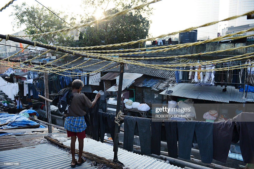 In this photograph taken on December 11, 2012 a worker hangs clothes to dry on lines crowding tin roofs over an open air laundry facility known as the Dhobi Ghat in Mumbai. This 25-acre (10-hectare) space is a chaotic conglomeration of rows of open-air concrete wash pens, each with its own flogging stone and rooms where the washermen, also known as 'dhobiwallahs', sleep and work. Many of the over 700 families that make a living out of this Dhobi Ghat, who had followed their father into the business, a life of dunking, thrashing and drying close to 1,000 items of clothing each day for just 7 USD, are worried about the future as the workload has gone down considerably. Most ordinary Indians who have seen their disposable incomes rise as the country's economy expands, have dispensed with the services of the dhobiwallahs for good since most modern homes are equipped with a washing machine. AFP PHOTO / Roberto Schmidt