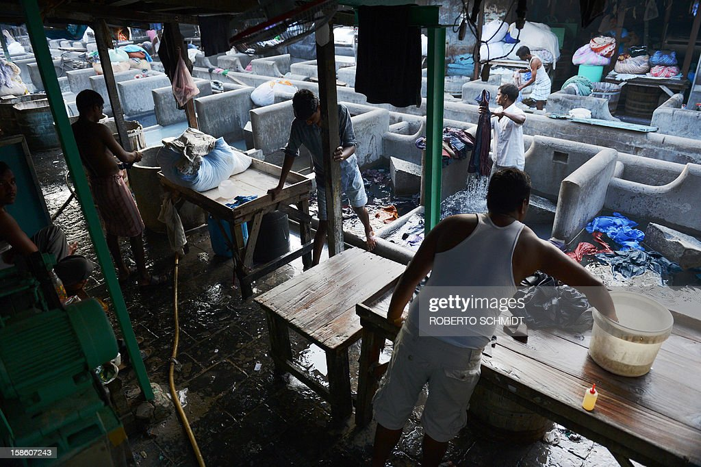 In this photograph taken on December 11, 2012 washers clean clothes at an open air laundry facility known as the Dhobi Ghat in Mumbai. This 25-acre (10-hectare) space is a chaotic conglomeration of rows of open-air concrete wash pens, each with its own flogging stone and rooms where the washermen, also known as 'dhobiwallahs', sleep and work. Many of the over 700 families that make a living out of this Dhobi Ghat, who had followed their father into the business, a life of dunking, thrashing and drying close to 1,000 items of clothing each day for just 7 USD, are worried about the future as the workload has gone down considerably. Most ordinary Indians who have seen their disposable incomes rise as the country's economy expands, have dispensed with the services of the dhobiwallahs for good since most modern homes are equipped with a washing machine. AFP PHOTO / Roberto Schmidt