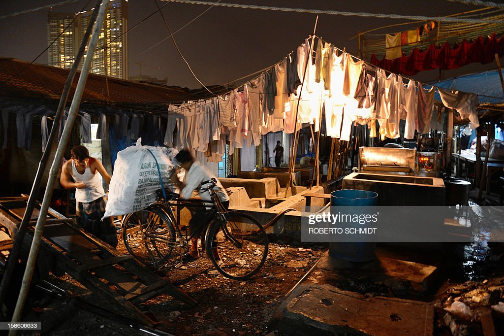 In this photograph taken on December 11, 2012 workers load a bag of clean clothes to be delivered to their owners on the back of a bicycle at an open air laundry facility known as the Dhobi Ghat in Mumbai. This 25-acre (10-hectare) space is a chaotic conglomeration of rows of open-air concrete wash pens, each with its own flogging stone and rooms where the washermen, also known as 'dhobiwallahs', sleep and work. Many of the over 700 families that make a living out of this Dhobi Ghat, who had followed their father into the business, a life of dunking, thrashing and drying close to 1,000 items of clothing each day for just 7 USD, are worried about the future as the workload has gone down considerably. Most ordinary Indians who have seen their disposable incomes rise as the country's economy expands, have dispensed with the services of the dhobiwallahs for good since most modern homes are equipped with a washing machine. AFP PHOTO / Roberto Schmidt