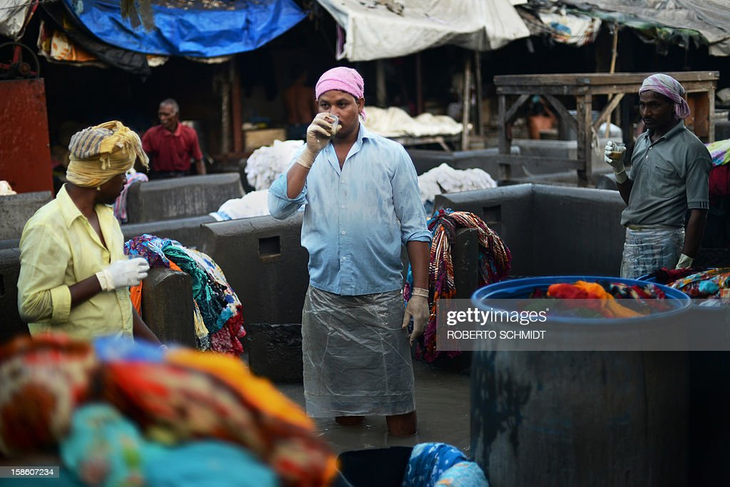 In this photograph taken on December 11, 2012 workers sip tea during a short break from washing clothes at an open air laundry facility known as the Dhobi Ghat in Mumbai. This 25-acre (10-hectare) space is a chaotic conglomeration of rows of open-air concrete wash pens, each with its own flogging stone and rooms where the washermen, also known as 'dhobiwallahs', sleep and work. Many of the over 700 families that make a living out of this Dhobi Ghat, who had followed their father into the business, a life of dunking, thrashing and drying close to 1,000 items of clothing each day for just 7 USD, are worried about the future as the workload has gone down considerably. Most ordinary Indians who have seen their disposable incomes rise as the country's economy expands, have dispensed with the services of the dhobiwallahs for good since most modern homes are equipped with a washing machine. AFP PHOTO / Roberto Schmidt