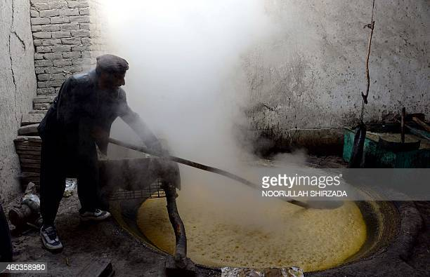 In this photograph taken on December 11 2014 an Afghan labourer prepares brown sugar from sugarcane juice at a factory in the Kama district near...