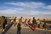 In this photograph taken on December 11 2014 soldiers watch fellow soldiers play a friendly game of football against members of the Afghan police at...