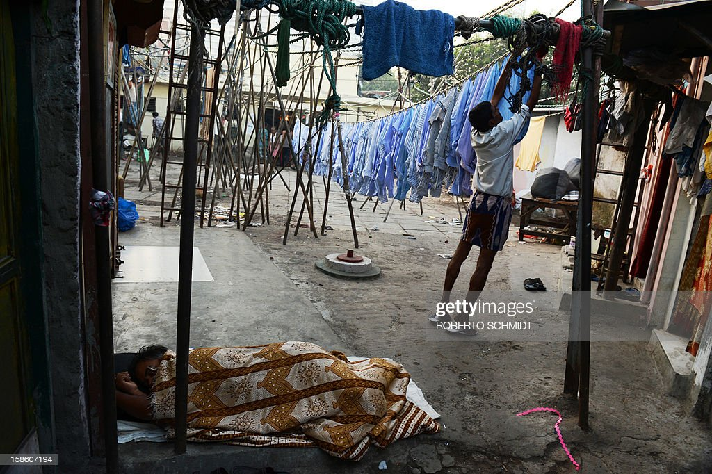 In this photograph taken on December 13, 2012 a man hangs shirts to dry as another one sleeps on the floor of an open air laundry facility known as the Dhobi Ghat in Mumbai. This 25-acre (10-hectare) space is a chaotic conglomeration of rows of open-air concrete wash pens, each with its own flogging stone and rooms where the washermen, also known as 'dhobiwallahs', sleep and work. Many of the over 700 families that make a living out of this Dhobi Ghat, who had followed their father into the business, a life of dunking, thrashing and drying close to 1,000 items of clothing each day for just 7 USD, are worried about the future as the workload has gone down considerably. Most ordinary Indians who have seen their disposable incomes rise as the country's economy expands, have dispensed with the services of the dhobiwallahs for good since most modern homes are equipped with a washing machine. AFP PHOTO / Roberto Schmidt