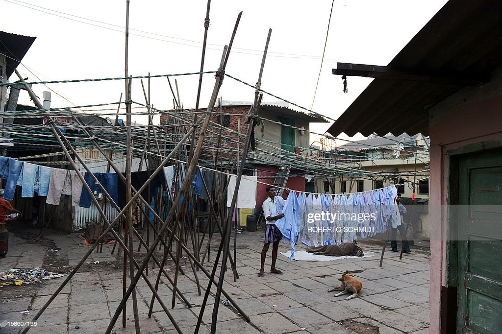 In this photograph taken on December 13, 2012 a man hangs shirts to dry an open air laundry facility known as the Dhobi Ghat in Mumbai. This 25-acre (10-hectare) space is a chaotic conglomeration of rows of open-air concrete wash pens, each with its own flogging stone and rooms where the washermen, also known as 'dhobiwallahs', sleep and work. Many of the over 700 families that make a living out of this Dhobi Ghat, who had followed their father into the business, a life of dunking, thrashing and drying close to 1,000 items of clothing each day for just 7 USD, are worried about the future as the workload has gone down considerably. Most ordinary Indians who have seen their disposable incomes rise as the country's economy expands, have dispensed with the services of the dhobiwallahs for good since most modern homes are equipped with a washing machine. AFP PHOTO / Roberto Schmidt