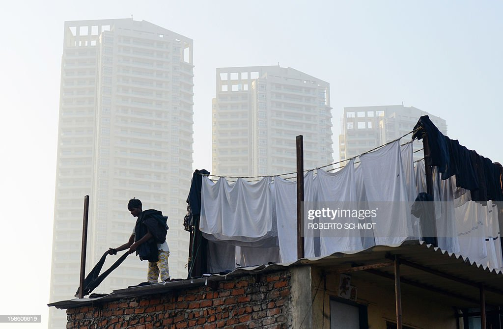 In this photograph taken on December 13, 2012 a man lays pants to dry on a tin roof at an open air laundry facility known as the Dhobi Ghat near residential luxury highrises in Mumbai. This 25-acre (10-hectare) space is a chaotic conglomeration of rows of open-air concrete wash pens, each with its own flogging stone and rooms where the washermen, also known as 'dhobiwallahs', sleep and work. Many of the over 700 families that make a living out of this Dhobi Ghat, who had followed their father into the business, a life of dunking, thrashing and drying close to 1,000 items of clothing each day for just 7 USD, are worried about the future as the workload has gone down considerably. Most ordinary Indians who have seen their disposable incomes rise as the country's economy expands, have dispensed with the services of the dhobiwallahs for good since most modern homes are equipped with a washing machine. AFP PHOTO / Roberto Schmidt