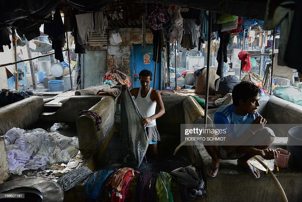 In this photograph taken on December 13, 2012 a man washes clothes as another one brushes his teeth in the early morning at an open air laundry facility known as the Dhobi Ghat in Mumbai. This 25-acre (10-hectare) space is a chaotic conglomeration of rows of open-air concrete wash pens, each with its own flogging stone and rooms where the washermen, also known as 'dhobiwallahs', sleep and work. Many of the over 700 families that make a living out of this Dhobi Ghat, who had followed their father into the business, a life of dunking, thrashing and drying close to 1,000 items of clothing each day for just 7 USD, are worried about the future as the workload has gone down considerably. Most ordinary Indians who have seen their disposable incomes rise as the country's economy expands, have dispensed with the services of the dhobiwallahs for good since most modern homes are equipped with a washing machine. AFP PHOTO / Roberto Schmidt