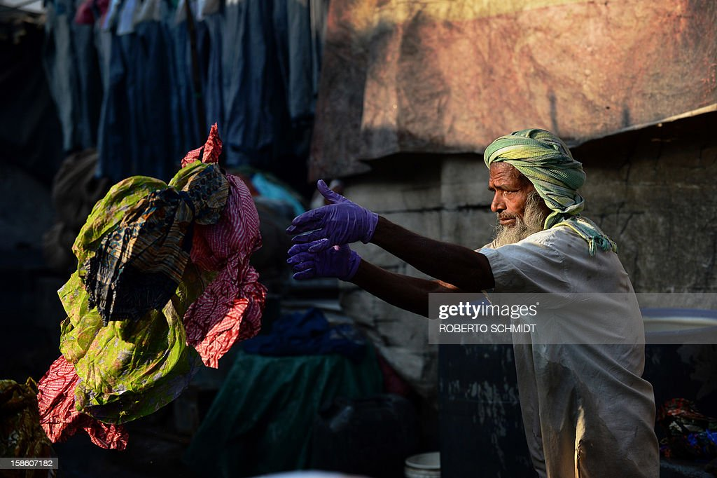 In this photograph taken on December 13, 2012 a washer throws clothes to be washed into his washing pen at an open air laundry facility known as the Dhobi Ghat in Mumbai. This 25-acre (10-hectare) space is a chaotic conglomeration of rows of open-air concrete wash pens, each with its own flogging stone and rooms where the washermen, also known as 'dhobiwallahs', sleep and work. Many of the over 700 families that make a living out of this Dhobi Ghat, who had followed their father into the business, a life of dunking, thrashing and drying close to 1,000 items of clothing each day for just 7 USD, are worried about the future as the workload has gone down considerably. Most ordinary Indians who have seen their disposable incomes rise as the country's economy expands, have dispensed with the services of the dhobiwallahs for good since most modern homes are equipped with a washing machine. AFP PHOTO / Roberto Schmidt