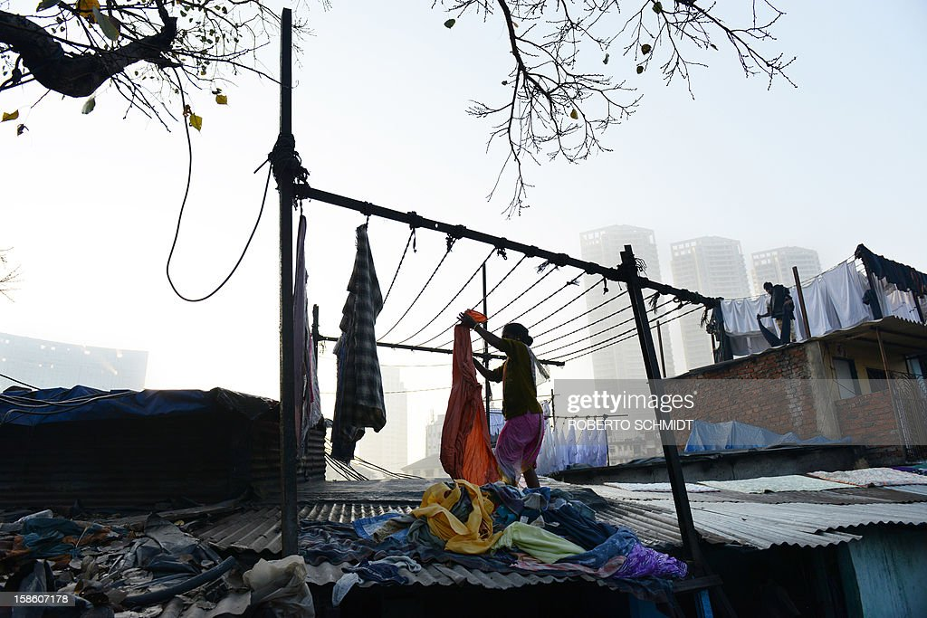 In this photograph taken on December 13, 2012 a woman hangs clean clothes to dry at an open air laundry facility known as the Dhobi Ghat near luxury residential highrises in Mumbai. This 25-acre (10-hectare) space is a chaotic conglomeration of rows of open-air concrete wash pens, each with its own flogging stone and rooms where the washermen, also known as 'dhobiwallahs', sleep and work. Many of the over 700 families that make a living out of this Dhobi Ghat, who had followed their father into the business, a life of dunking, thrashing and drying close to 1,000 items of clothing each day for just 7 USD, are worried about the future as the workload has gone down considerably. Most ordinary Indians who have seen their disposable incomes rise as the country's economy expands, have dispensed with the services of the dhobiwallahs for good since most modern homes are equipped with a washing machine. AFP PHOTO / Roberto Schmidt
