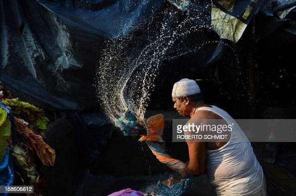 In this photograph taken on December 13 2012 an Indian washer whips a bunch of wet clothes into a stone at an open air laundry facility known as the...