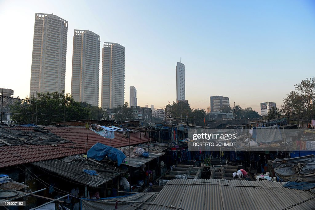 In this photograph taken on December 13, 2012 luxury residential highrises loom over an open air laundry facility known as the Dhobi Ghat in Mumbai. This 25-acre (10-hectare) space is a chaotic conglomeration of rows of open-air concrete wash pens, each with its own flogging stone and rooms where the washermen, also known as 'dhobiwallahs', sleep and work. Many of the over 700 families that make a living out of this Dhobi Ghat, who had followed their father into the business, a life of dunking, thrashing and drying close to 1,000 items of clothing each day for just 7 USD, are worried about the future as the workload has gone down considerably. Most ordinary Indians who have seen their disposable incomes rise as the country's economy expands, have dispensed with the services of the dhobiwallahs for good since most modern homes are equipped with a washing machine. AFP PHOTO / Roberto Schmidt