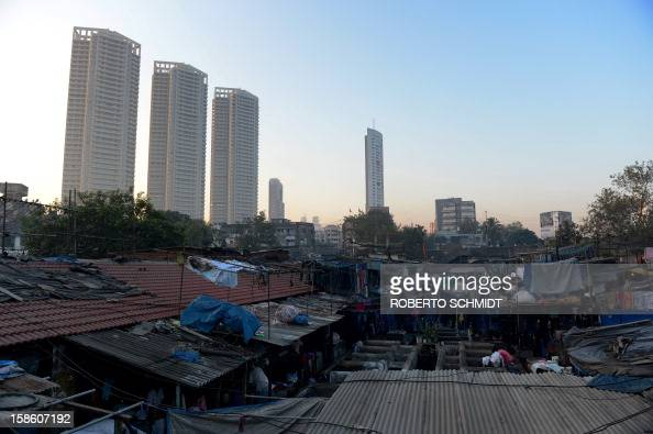 In this photograph taken on December 13 2012 luxury residential highrises loom over an open air laundry facility known as the Dhobi Ghat in Mumbai...