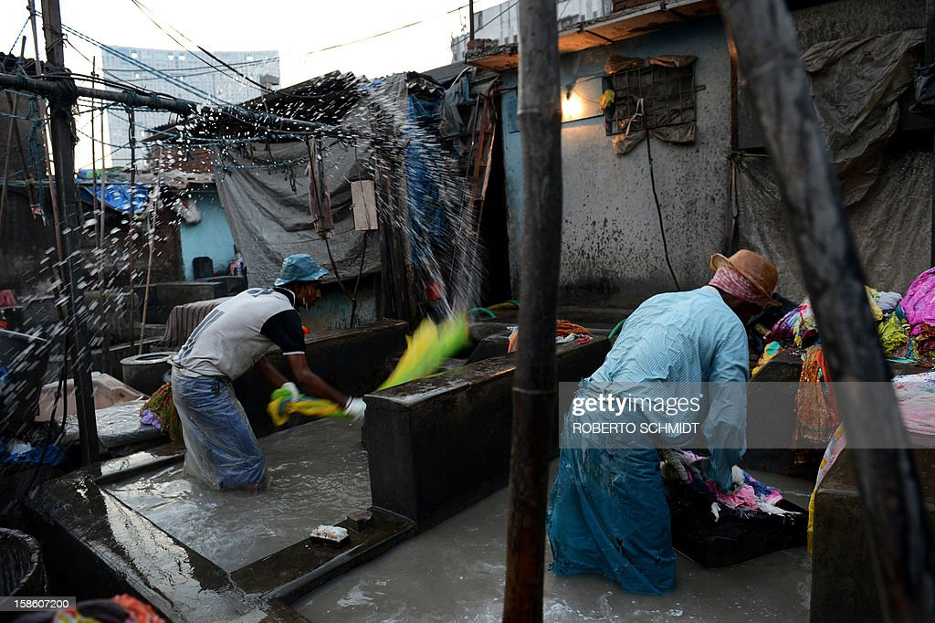 In this photograph taken on December 13, 2012 men wash clothes at an open air laundry facility known as the Dhobi Ghat in Mumbai. This 25-acre (10-hectare) space is a chaotic conglomeration of rows of open-air concrete wash pens, each with its own flogging stone and rooms where the washermen, also known as 'dhobiwallahs', sleep and work. Many of the over 700 families that make a living out of this Dhobi Ghat, who had followed their father into the business, a life of dunking, thrashing and drying close to 1,000 items of clothing each day for just 7 USD, are worried about the future as the workload has gone down considerably. Most ordinary Indians who have seen their disposable incomes rise as the country's economy expands, have dispensed with the services of the dhobiwallahs for good since most modern homes are equipped with a washing machine. AFP PHOTO / Roberto Schmidt