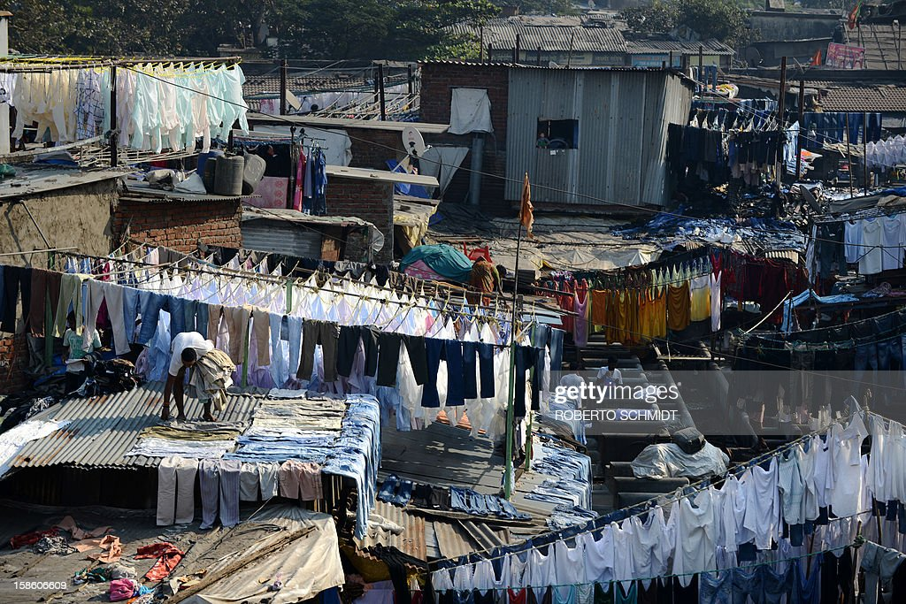 In this photograph taken on December 13, 2012, an Indian worker picks up dried clothes from a tin roof at an open air laundry facility known as the Dhobi Ghat in Mumbai. This 25-acre (10-hectare) space is a chaotic conglomeration of rows of open-air concrete wash pens, each with its own flogging stone and rooms where the washermen, also known as 'dhobiwallahs', sleep and work. Many of the over 700 families that make a living out of this Dhobi Ghat, who had followed their father into the business, a life of dunking, thrashing and drying close to 1,000 items of clothing each day for just 7 USD, are worried about the future as the workload has gone down considerably. Most ordinary Indians who have seen their disposable incomes rise as the country's economy expands, have dispensed with the services of the dhobiwallahs for good since most modern homes are equipped with a washing machine. AFP PHOTO / Roberto Schmidt