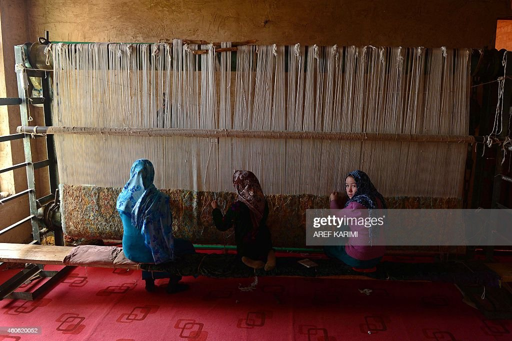 In this photograph taken on December 17, 2014 young Afghan girls weave a carpet at a carpet manufacturer in Herat. Some 42,500 women and their families are involved in the project which aims to provide a means of subsistence and potentially lead to international market access for silk producers in the country. Western Afghanistan, once a stop along the Silk Road trade route, has a long tradition in the silk production process dating back thousands of years. Carpets are Afghanistan's best-known export, woven mostly by women and children in the north of the country, a trade which once employed, directly or indirectly, six million people, or a fifth of the country's population, but that figure has dropped sharply. The popular wool and silk Afghan carpets made by different tribes sells from between 150 - 1,000 US dollars. AFP PHOTO/Aref Karimi