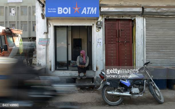 In this photograph taken on December 19 an Indian man sits outside a cashless ATM machine in New Delhi An ATM in Delhi spewed dummy 2000rupee notes...