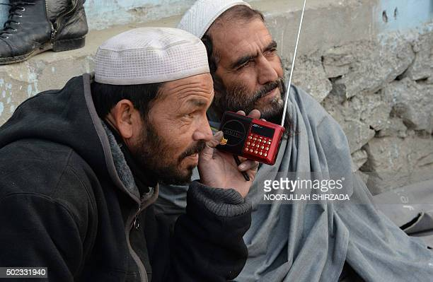 In this photograph taken on December 22 Afghan men listen to a radio broadcast run by the Islamic State group in Jalalabad The Islamic State group...