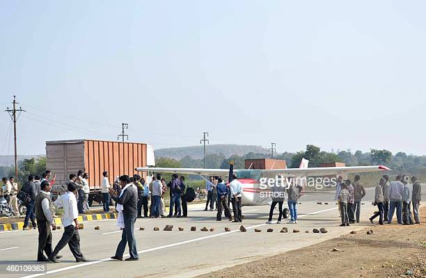 In this photograph taken on December 31 Indian officials and bystanders gather around a light aircraft after it landed on a public highway at Betul...