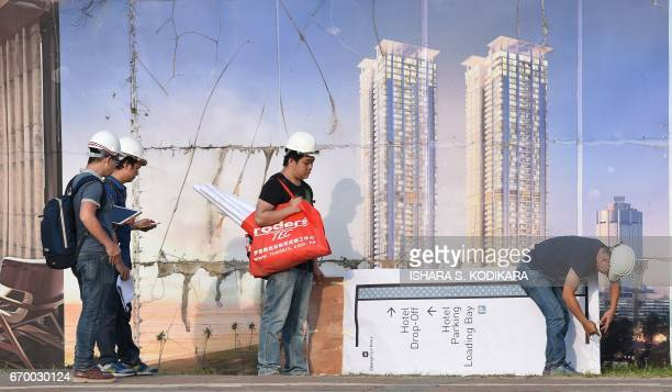 In this photograph taken on December 7 Chinese construction team members look on at a new apartment building complex in the Sri Lankan capital...