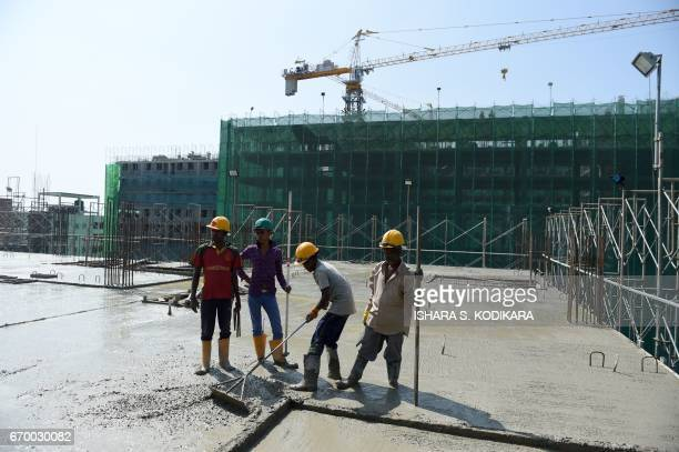 In this photograph taken on December 7 Sri Lankan construction labourers work on a new apartment building at a complex in Colombo Cheap Sri Lankan...