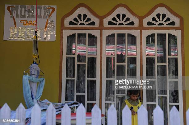 In this photograph taken on December 8 a banner welcoming wedding guests is seen on the wall of Yusra Fitriani's house in Pidie Jaya Aceh province On...