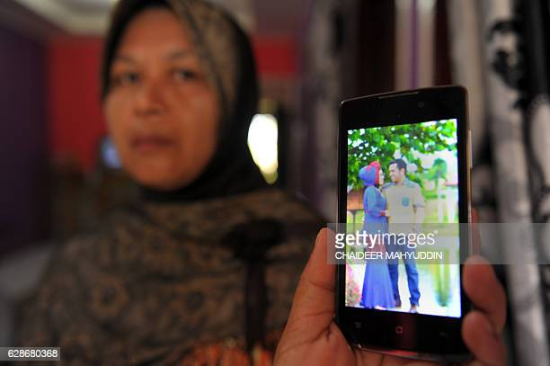 In this photograph taken on December 8 the mother of Yusra Fitriani shows a prewedding portrait photo of her daughter and groom in Pidie Jaya Aceh...