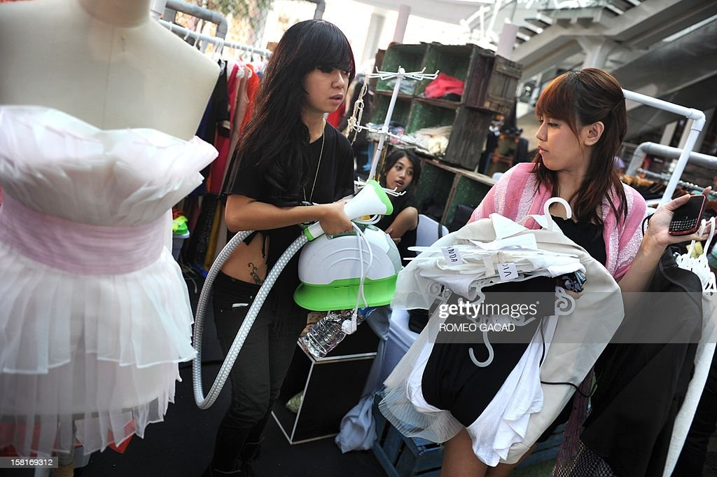 In this photograph taken on December 9, 2012 Indonesian fashion designer Selphie Usagi, 21, (L) and Viva (R), an assistant prepares for a fashion show during a weekend fashion bazaar at Epicentrum, a new Jakarta commercial center. Many young Indonesian designers are breaking into Indonesia's huge fashion market as the country enjoys economic growth and stability with local and foreign customers snapping up their designs sold from shops, bazaars and online. Designers are combining traditional fabric like batik with denim and other textile, creating a variety of hip and sexy looks to trendy conservative wear, with fashionable Muslim women going for full body covered dresses while others adopt to bold western outfits.