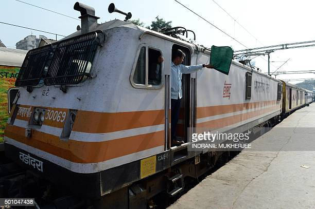 In this photograph taken on December 9 an Indian locomotive driver of the Ahmedabad bound Karnavati Express waves a green flag as he signals the...